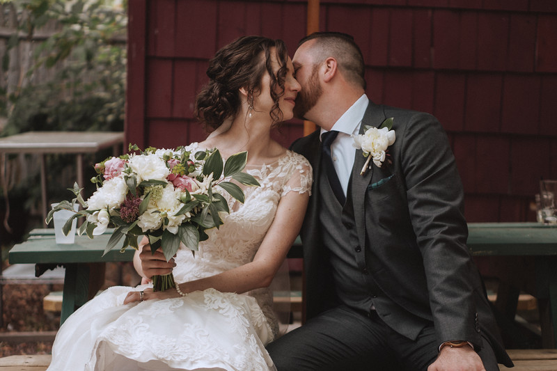 The groom leans over and whispers a secret into the brides ear.