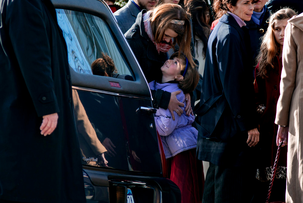 Description of . A child is embraced near a hearse carrying teacher Anne Marie Murphy, who was killed at the Sandy Hook Elementary School shootings in Newtown, after a funeral at St. Mary Of The Assumption Church  in Katonah, N.Y. Thursday, Dec. 20, 2012.  Murphy was killed when Adam Lanza, walked into Sandy Hook Elementary School in Newtown, Conn., Dec. 14, and opened fire, killing 26, including 20 children, before killing himself. (AP Photo/Craig Ruttle)