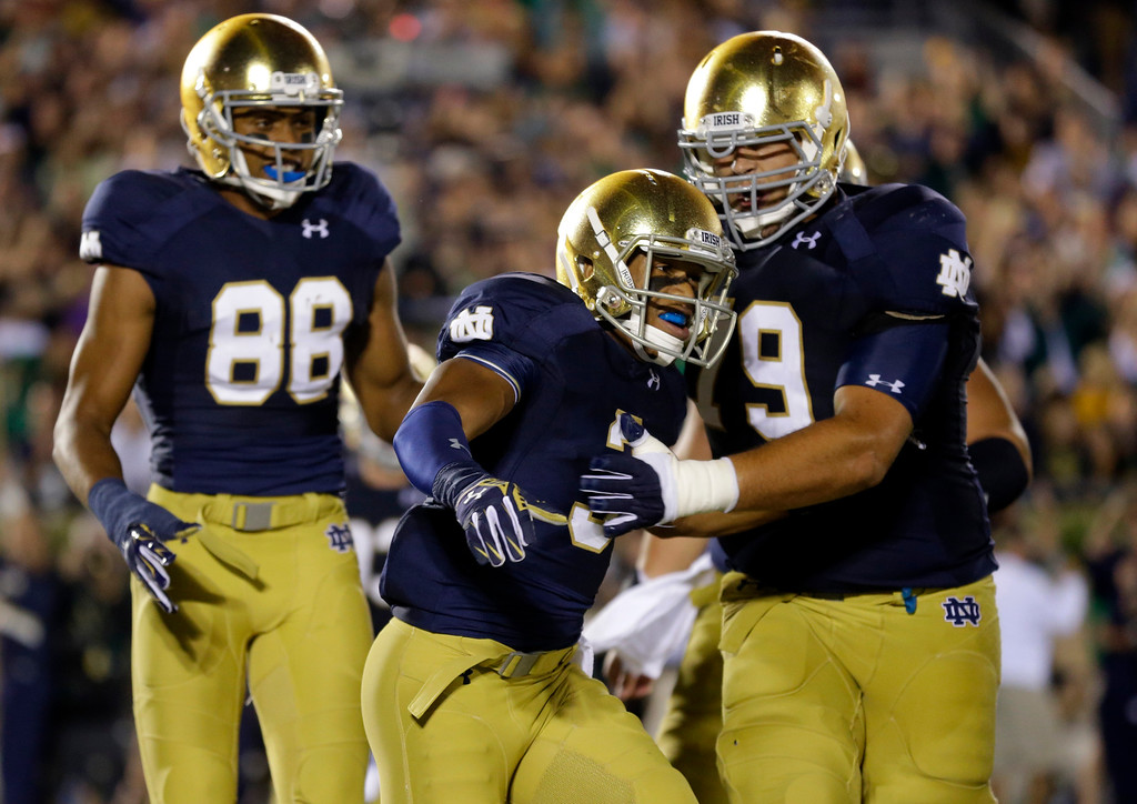 . Notre Dame wide receiver Amir Carlisle, center, celebrates a touchdown with offensive linesman Steve Elmer, right, and wide receiver Buster Sheridan during the second half of an NCAA college football game against Michigan in South Bend, Ind., Saturday, Sept. 6, 2014. (AP Photo/Michael Conroy)