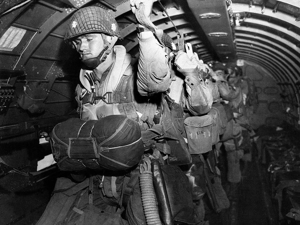 Description of . U.S. paratroopers fix their static lines for a jump before dawn over Normandy, France on D-Day, in this June 6, 1944 file photo. (AP Photo/Army Signal Corps, File)
