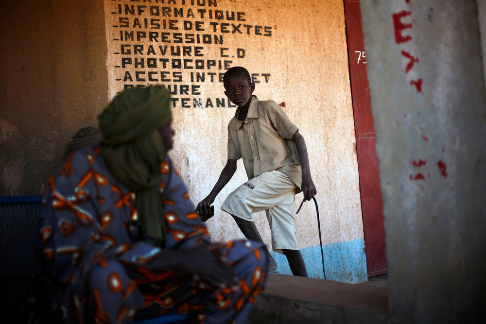 . A young Malian boy greets elders in Gao, northern Mali, Thursday Feb. 7, 2013. French troops began to withdraw from Timbuktu Thursday after securing the fabled city as they ramped up their mission in another northern Mali city, searching for Islamic extremists who may be mixing among the local population. (AP Photo/Jerome Delay)