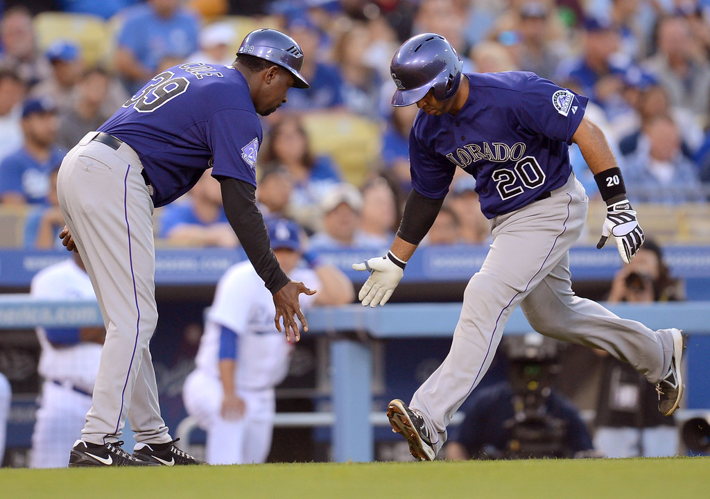 . Wilin Rosario of the Colordao Rockies is congratulated by thirdbase coach Stu Cole after hitting a 3 run homerun in the 1st inning April 29, 2013 in Los Angeles, CA.(Andy Holzman/Staff Photographer)