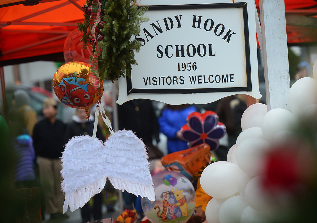 . A pair of angel wings and balloons stand after being offered at a makeshift shrine to the victims of a elementary school shooting in Newtown, Connecticut, December 16, 2012.  A young gunman slaughtered 20 small children and six teachers on December 14,2012 after walking into a school in an idyllic Connecticut town wielding at least two sophisticated firearms. EMMANUEL DUNAND/AFP/Getty Images