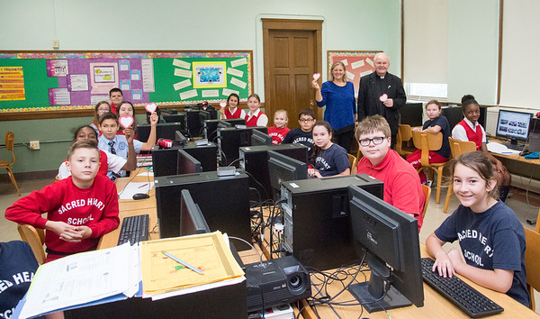 10/17/19 Wesley Bunnell | StaffrrFifth through eight grade students at Sacred Heart School pose for a photo in the computer lab along with School Principal Kathy Muller and Monsignor Daniel J. Plocharczyk, Pastor of Sacred Heart Church.