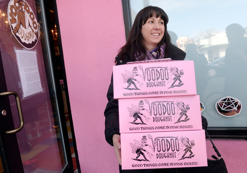 . Ashton Preble carried away three dozen doughnuts as Voodoo Doughnut,  a new business from Oregon,  held its grand opening on Wednesday, January 15, 2014. Denver Mayor Michael Hancock was on hand to welcome Voodoo, it\'s new location at 1520 E. Colfax Ave. in Denver.  (Denver Post Photo by Cyrus McCrimmon)