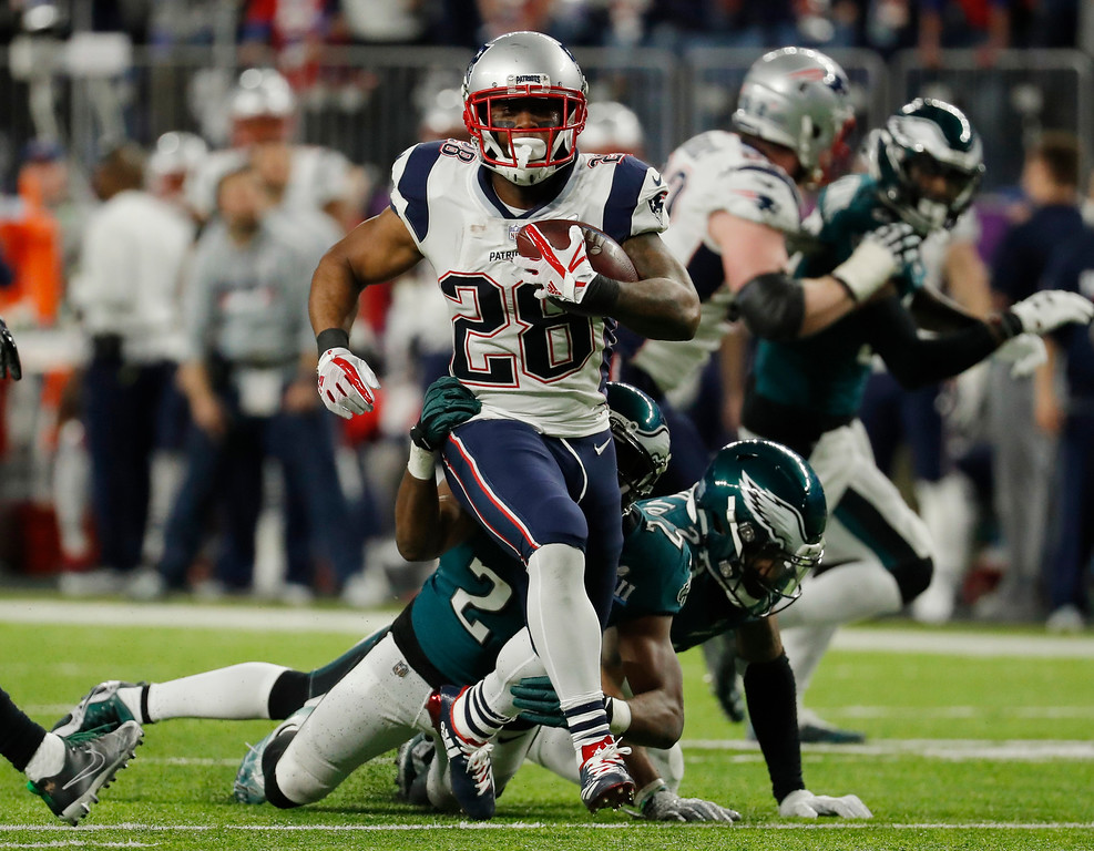 . New England Patriots running back James White (28) runs away from Philadelphia Eagles defensive back Corey Graham (24), for a touchdown during the first half of the NFL Super Bowl 52 football game Sunday, Feb. 4, 2018, in Minneapolis. (AP Photo/Charlie Neibergall)