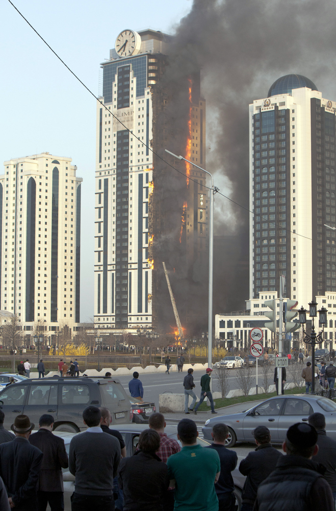 . Chechens watch a burning skyscraper  in central Grozny on April 3, 2013. A fire raged in a skyscraper in the Chechnya capital Grozny on Wednesday, a building which is a centrepiece of a drive by local authorities to promote the city as a glitzy and modern hub. The buildng is uninhabited.  ELENA FITKULINA/AFP/Getty Images