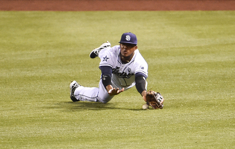 . Rymer Liriano #7 of the San Diego Padres can\'t make a diving catch on a single hit by Justin Morneau #33 of the Colorado Rockies during the third inning of a baseball game at Petco Park August, 11, 2014 in San Diego, California.  (Photo by Denis Poroy/Getty Images)