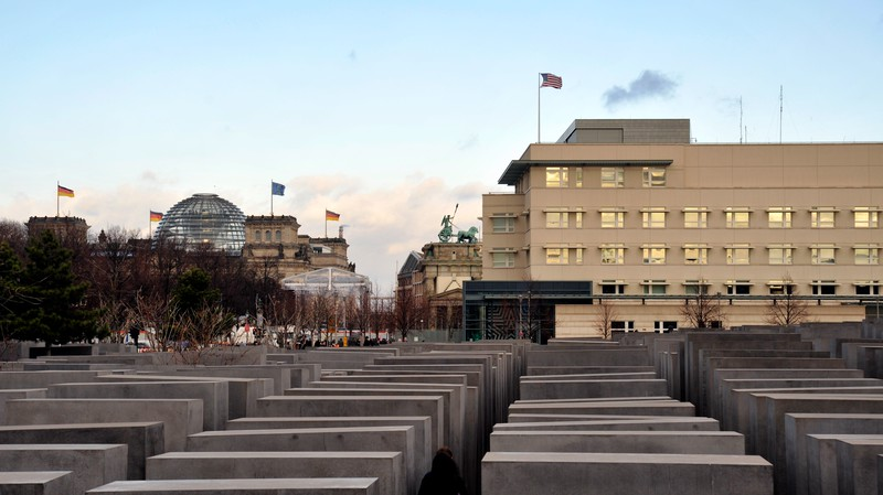 Looking across the Holocaust Memorial with the American Embassy in the middle ground, the Brandenburg Gate behind and the Reichstag Building in the left background.