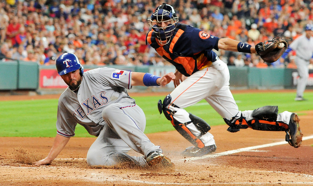 . Texas Rangers\' Bobby Wilson, left, beats the tag of Houston Astros catcher Jason Castro to score a run on Ian Desmond\'s RBI-single during the third inning of a baseball game, Sunday, May 22, 2016, in Houston. (AP Photo/Eric Christian Smith)