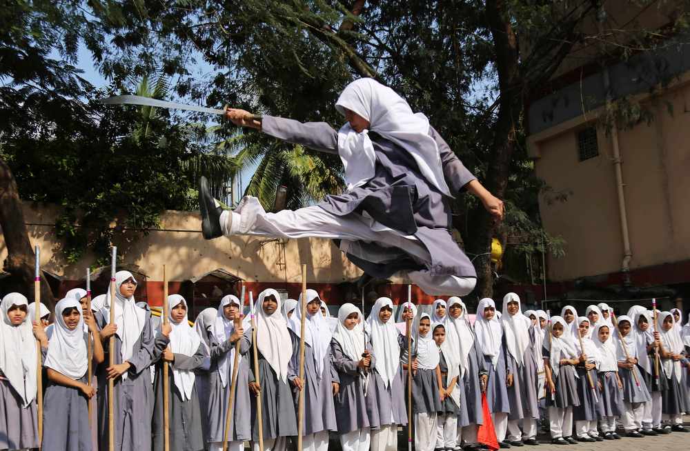 Description of . An Indian Muslim girl performs martial arts during a function to mark International Women's Day at a school in Hyderabad, India, Friday, March 7, 2014. International Women's Day will be marked on March 8. (AP Photo/Mahesh Kumar A.)