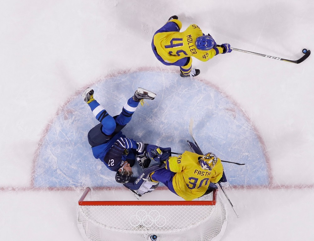 . Petri Kontiola, of Finland, left, slides into goalie Viktor Fasth, of Sweden, as teammate Oscar Moller, above, clears the puck during the third period of the preliminary round of the men\'s hockey game at the 2018 Winter Olympics in Gangneung, South Korea, Sunday, Feb. 18, 2018. (AP Photo/Frank Franklin II)