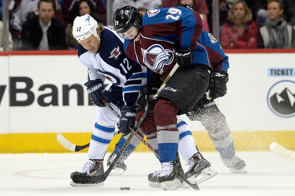 . Olli Jokinen (12) of the Winnipeg Jets defends Nathan MacKinnon (29) of the Colorado Avalanche during the Avs\' 3-2 win. (Photo by AAron Ontiveroz/The Denver Post)