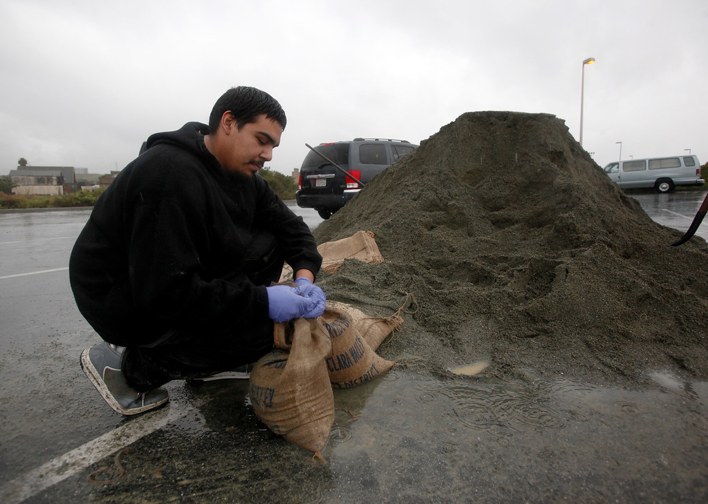 . Nathan Gonzalez fills sand bags to help prevent flooding at her grandmother\'s house in Alviso, Calif., Thursday,Dec. 11, 2014. (Karl Mondon/Bay Area News Group)