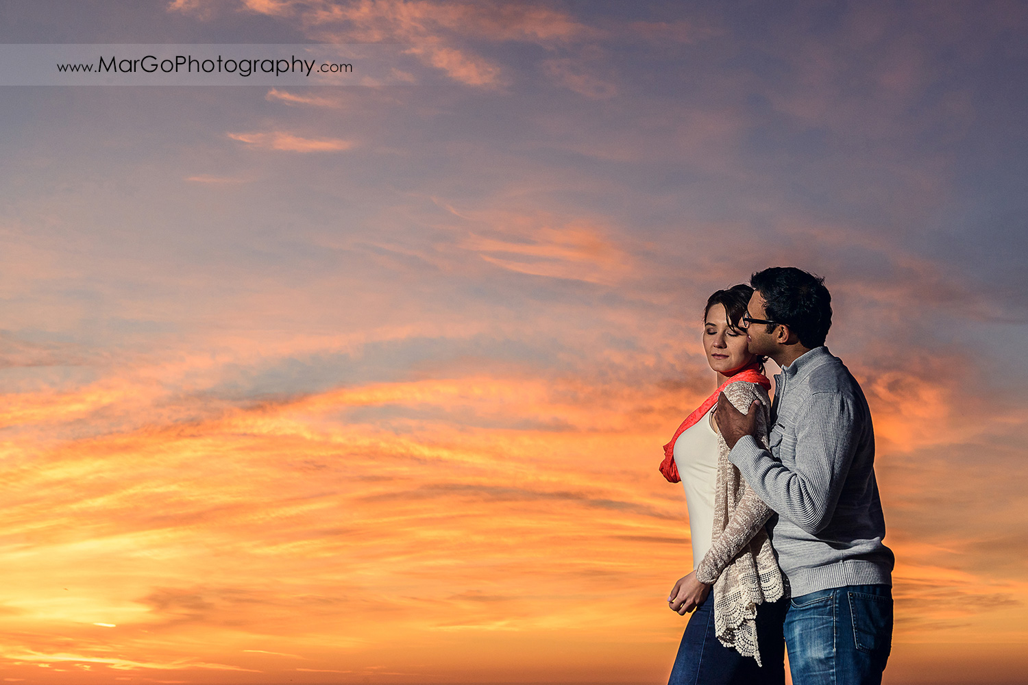 3/4 sunset portrait of man and woman in grey sweater and jeans during engagement session at San Francisco Baker Beach