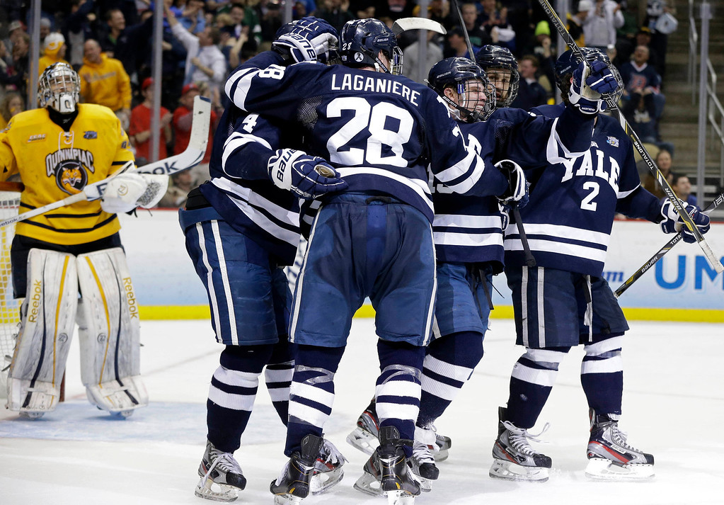 . Yale\'s Clinton Bourbonais, second from right, celebrates after his goal past Quinnipiac goalie Eric Hartzell, left, during the first period of the NCAA men\'s college hockey Frozen Four national championship game in Pittsburgh, Saturday, April 13, 2013. (AP Photo/Gene Puskar)