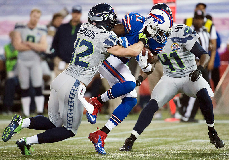 . Buffalo Bills wide receiver T.J.Graham (11) gets tackled by Seattle Seahawks safety Chris Maragos (42) and cornerback Byron Maxwell (41) during the second half of an NFL football game, Sunday, Dec. 16, 2012, in Toronto. The Seahawks won 50-17. (AP Photo/The Canadian Press, Nathan Denette)