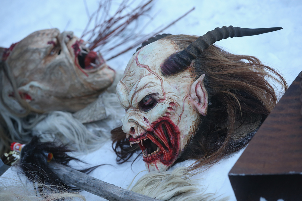 . Hand-crafted Krampus masks lie in the snow as participants dress as the Krampus creature prior to Krampus night on November 30, 2013 in Neustift im Stubaital, Austria. Sixteen Krampus groups including over 200 Krampuses participated in the first annual Neustift event. Krampus, in Tyrol also called Tuifl, is a demon-like creature represented by a fearsome, hand-carved wooden mask with animal horns, a suit made from sheep or goat skin and large cow bells attached to the waist that the wearer rings by running or shaking his hips up and down. Krampus has been a part of Central European, alpine folklore going back at least a millennium, and since the 17th-century Krampus traditionally accompanies St. Nicholas and angels on the evening of December 5 to visit households to reward children that have been good while reprimanding those who have not. However, in the last few decades Tyrol in particular has seen the founding of numerous village Krampus associations with up to 100 members each and who parade without St. Nicholas at Krampus events throughout November and early December.  (Photo by Sean Gallup/Getty Images)