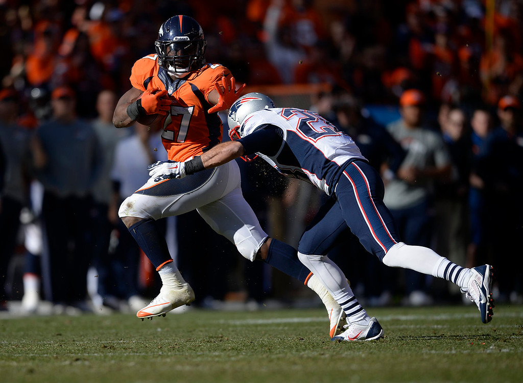 . Denver Broncos running back Knowshon Moreno (27) fights off a tackle by New England Patriots strong safety Steve Gregory (28) and gets a first down in the second quarter to set up a Broncos touchdown. The Denver Broncos take on the New England Patriots in the AFC Championship game at Sports Authority Field at Mile High in Denver on January 19, 2014. (Photo by AAron Ontiveroz/The Denver Post)