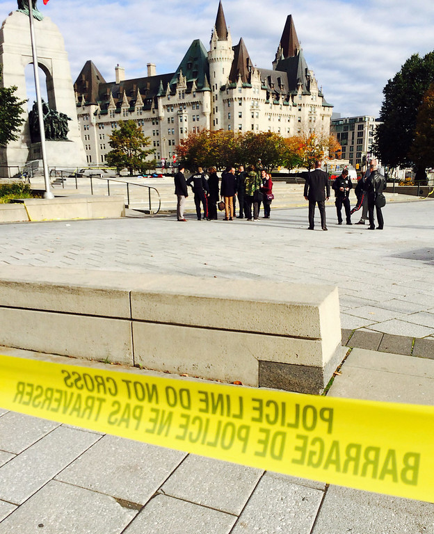 . Police tape surrounds the Canadian War Memorial in Ottawa on Wednesday Oct. 22, 2014.  A soldier standing guard at the National War Memorial  has been shot by an unknown gunman and people report hearing gunfire inside the halls of Parliament.  The gunman reportedly ran towards Parliament Hill, which is currently under lockdown and surrounded by security.  Prime Minister Stephen Harper was rushed away from the building to an undisclosed location, officials in his office said. (AP Photo/The Canadian Press, Jim Bronskill)