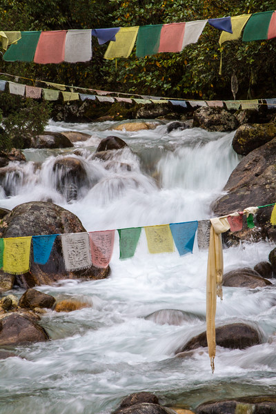 Buddhist prayer flags are strong across the river waterfall