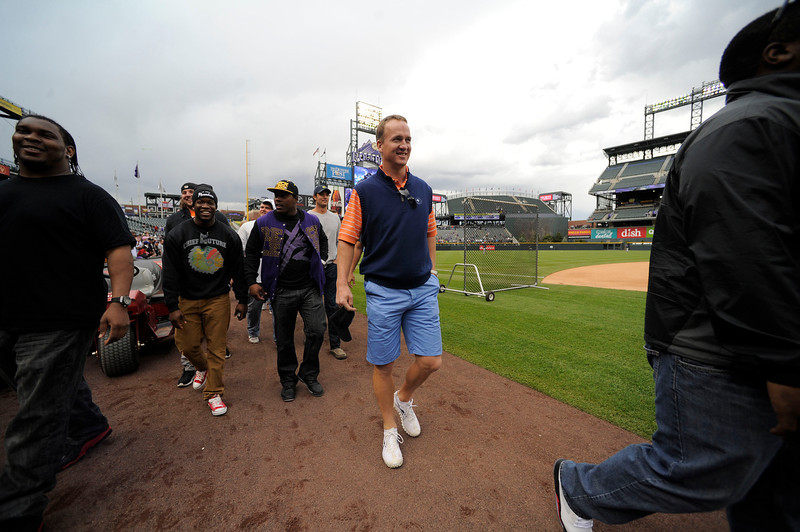 . Denver Broncos Peyton Manning walks down the warning track with some of the offensive line and a few defensive players to watch the Colorado Rockies New York Yankees batting practice May 7, 2013 at Coors Field. (Photo By John Leyba/The Denver Post)