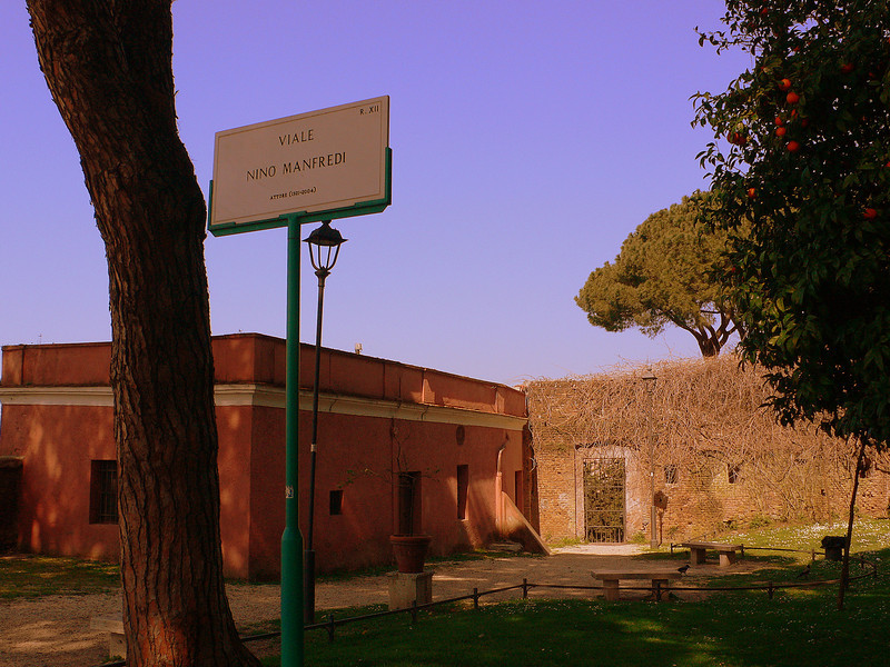The park next to the Santa Sabina. Roman street signs use a Serif font on clear white stone.