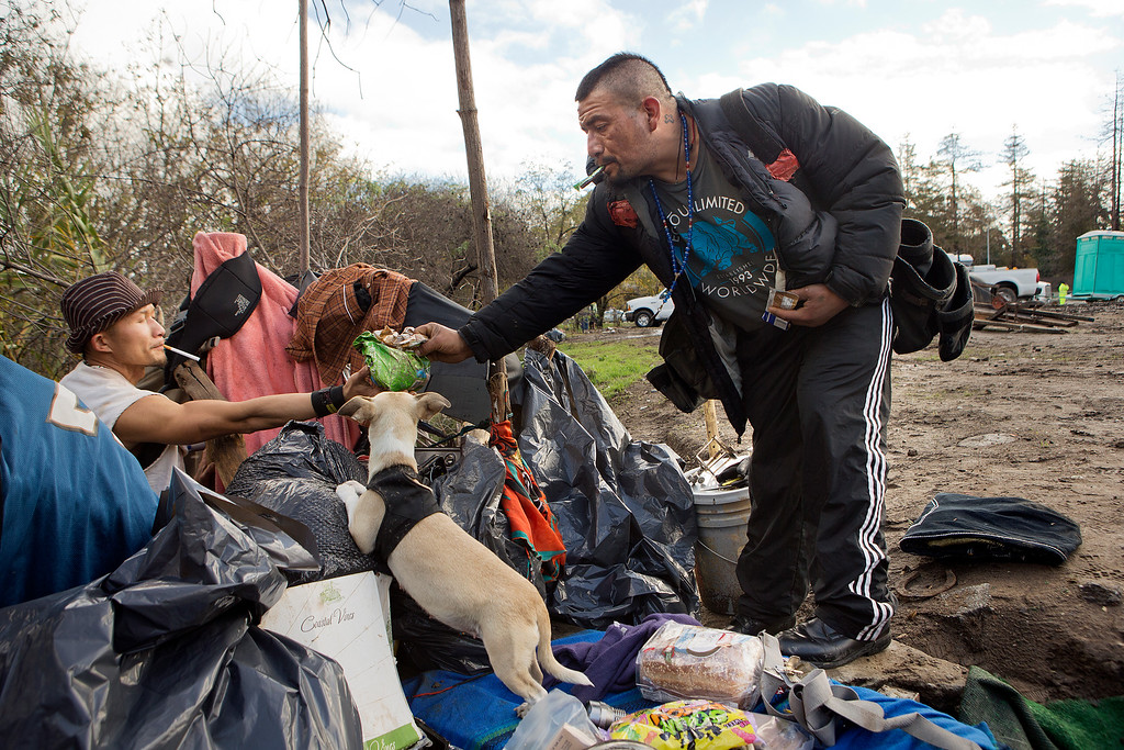 . At left, An Phuc Nguyen hands Valentin Cortez-Oseguer, right, dog food for his puppy before he leaves the homeless encampment known as The Jungle in San Jose, Calif., on Thursday, Dec. 4, 2014. (LiPo Ching/Bay Area News Group)