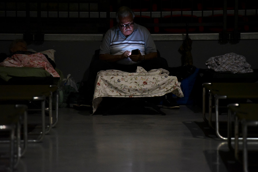 . A man watches his cell phone while waiting at Humacao Arena refugee center for the imminent impact of Maria, a Category 5 hurricane that threatens to hit the eastern region of the island with sustained winds of 175 miles per hour, in Humacao, Puerto Rico, Tuesday, September 19, 2017. About 137 citizens arrived at the refuge from different parts of the eastern region of the Island. (AP Photo/Carlos Giusti)