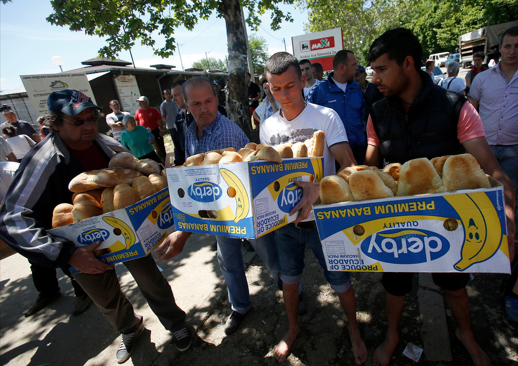 . Volunteers carry food for residents in Obrenovac, some 30 kilometers (18 miles) southwest of Belgrade, Serbia, Monday, May 19, 2014. Belgrade braced for a river surge Monday that threatened to inundate Serbia\'s main power plant and cause major power cuts in the crisis-stricken country as the Balkans struggle with the consequences of the worst flooding in southeastern Europe in more than a century. (AP Photo/Darko Vojinovic)