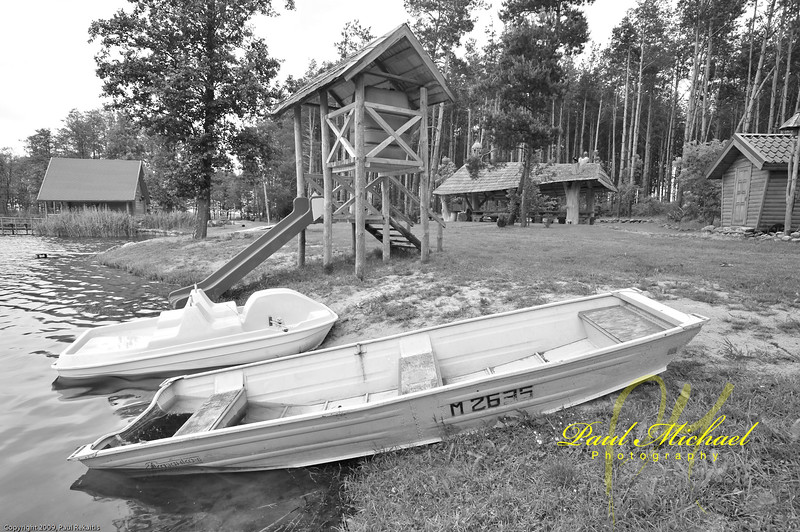 Two boats - Paddle boat and row boat.  Full of water because it rains so much in Lithuania.