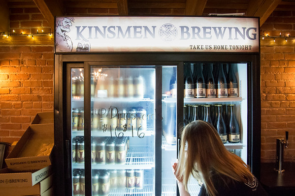 06/25/19 Wesley Bunnell | Staff Jessica Vitale of Kinsmen Brewing stocks the to go refrigerator at the brewery on Tuesday June 25, 2019. Governor Ned Lamont recently signed into law an increase in the amount of beer micro-breweries in Connecticut can sell to a customer from 9 liters to 9 gallons.