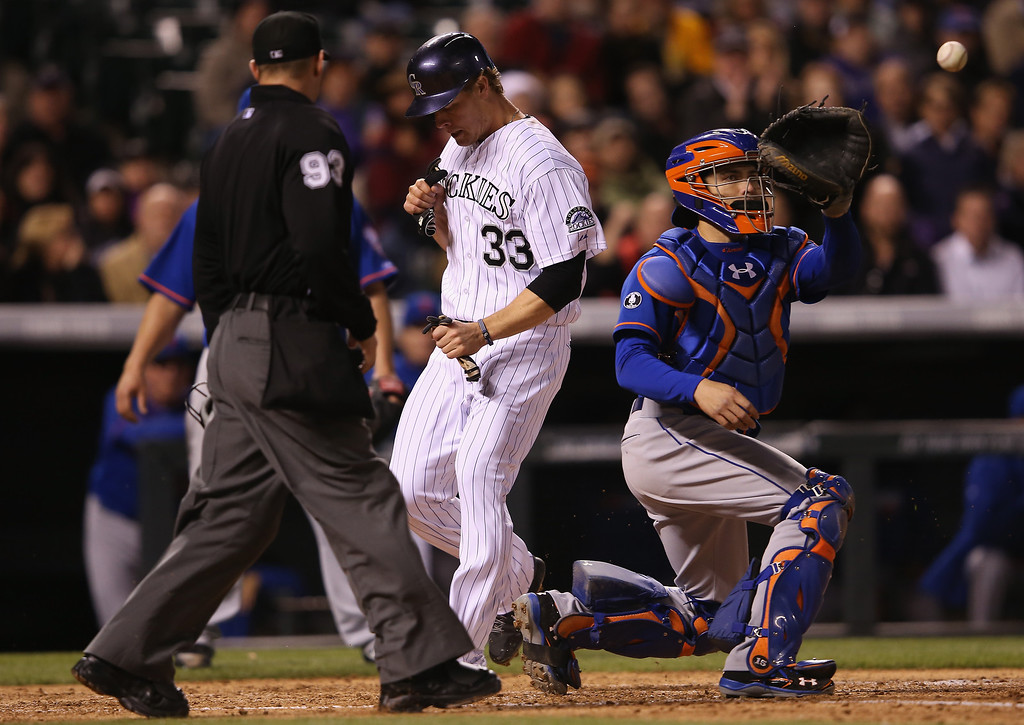 . Justin Morneau #33 of the Colorado Rockies scores on a triple by Corey Dickerson #6 of the Colorado Rockies as catcher Travis d\'Arnaud #15 of the New York Mets takes the late throw and umpire Will Little oversees the action as the Rockies take a 7-0 lead in the fifth inning at Coors Field on May 1, 2014 in Denver, Colorado.  (Photo by Doug Pensinger/Getty Images)