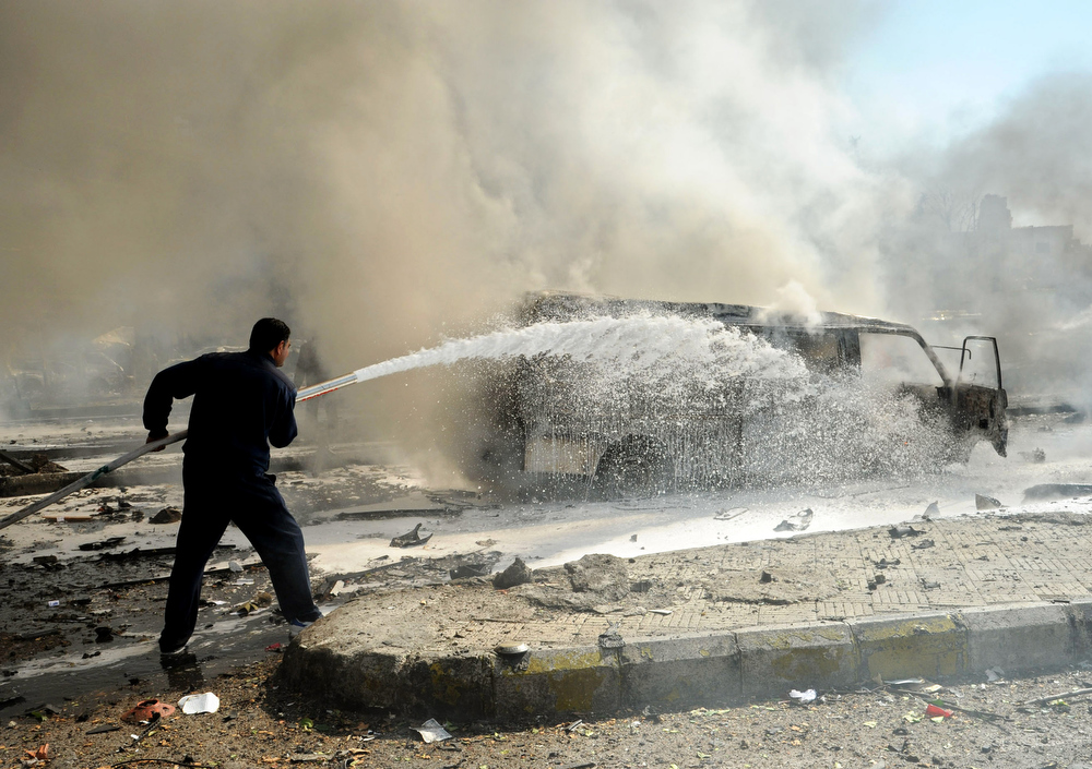 Description of . This photo released by the Syrian official news agency SANA, shows a Syrian fire fighter extinguishing burning cars after a huge explosion that shook central Damascus, Syria, Thursday, Feb. 21, 2013. A car bomb shook central Damascus on Thursday, exploding near the headquarters of the ruling Baath party and the Russian Embassy, eyewitnesses and opposition activists said. (AP Photo/SANA)