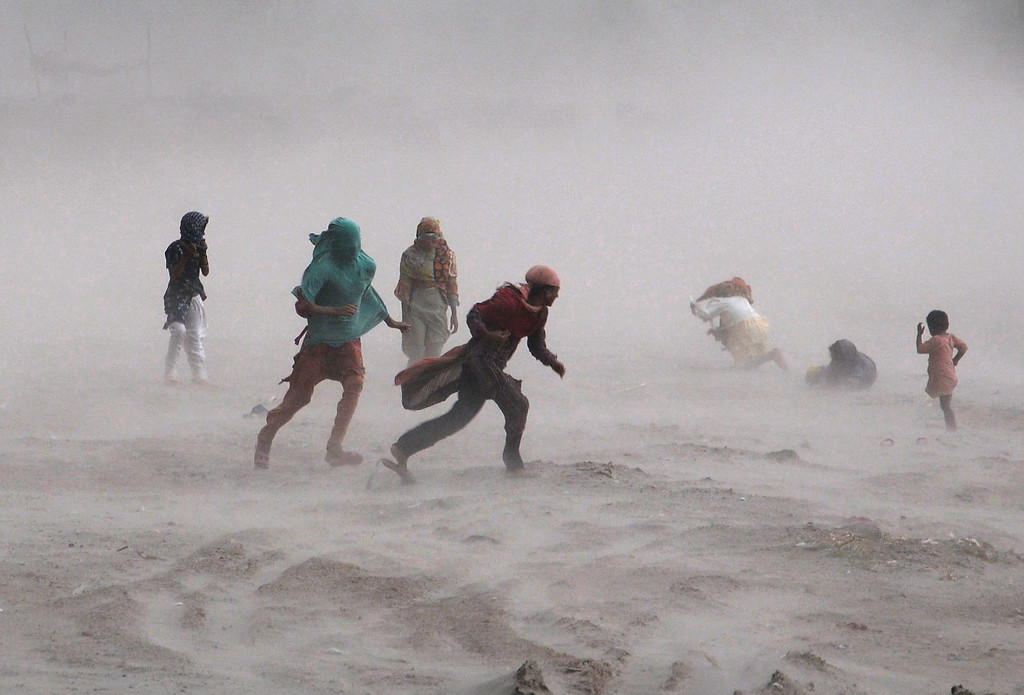 . Pakistani people walk through a storm near the Ravi river in Lahore on September 15, 2013. Heavy rains and hailstorms lashed the capital, throwing traffic out of gear in many parts of the city as a result of water logging.   Arif Ali/AFP/Getty Images