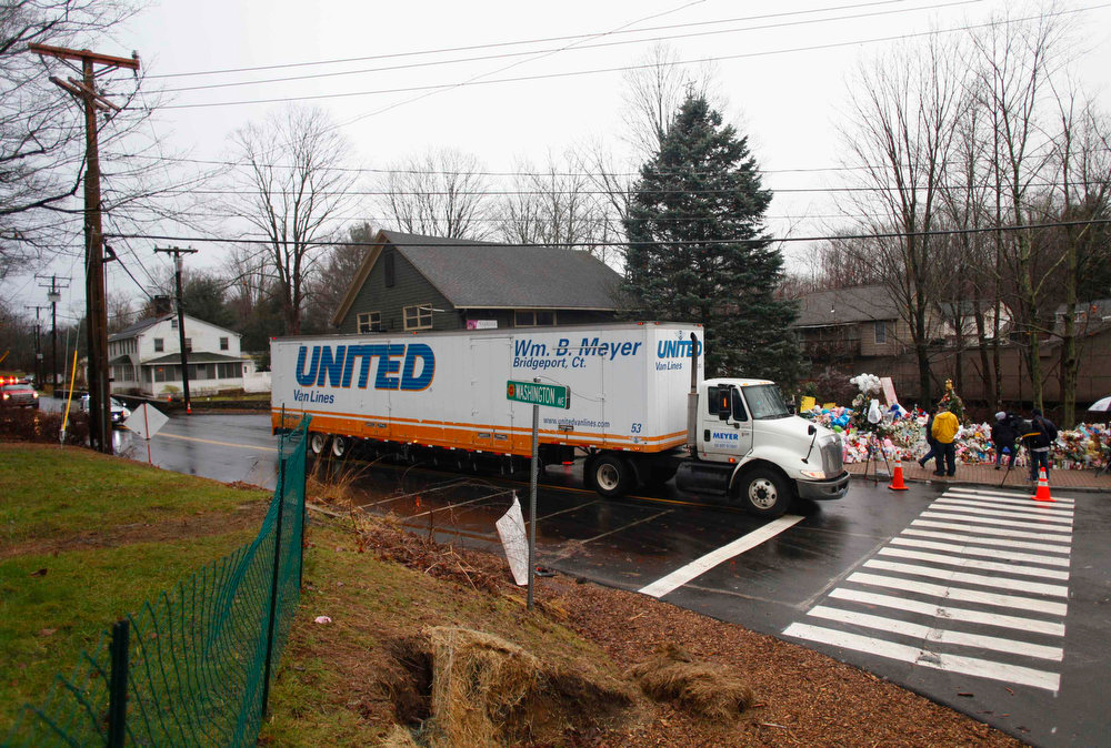 . A moving truck drives toward Sandy Hook Elementary School in Newtown, Connecticut December 18, 2012. U.S. Authorities continue to investigate the December 14 massacre in Connecticut in which a heavily armed gunman entered Sandy Hook Elementary school and shot and killed 20 children and six adults. The incident, resulting in 28 deaths, including the gunman and his mother, has prompted a fresh debate on U.S. gun control. REUTERS/Joshua Lott