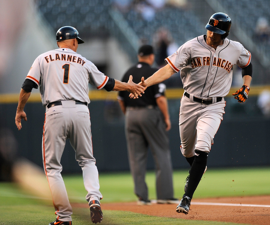 . San Francisco Giants\' Hunter Pence, right, is congratulated by third base coach Tim Flannery after hitting a two-run home run off Colorado Rockies starting pitcher Chad Bettis during the first inning of a baseball game on Tuesday, Aug. 27, 2013, in Denver. (AP Photo/Jack Dempsey)