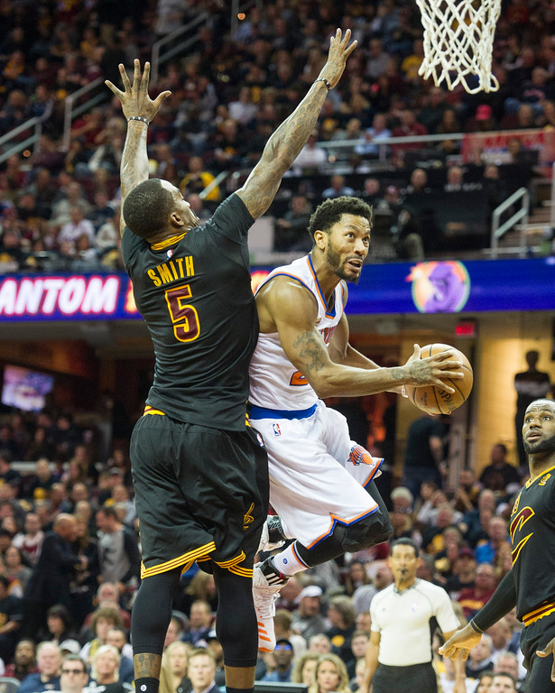 . New York Knicks\' Derrick Rose (25) drives past Cleveland Cavaliers� J.R. Smith (5) as Cavaliers LeBron James watches during the first half of a basketball game in Cleveland, Tuesday, Oct. 25, 2016. (AP Photo/Phil Long)