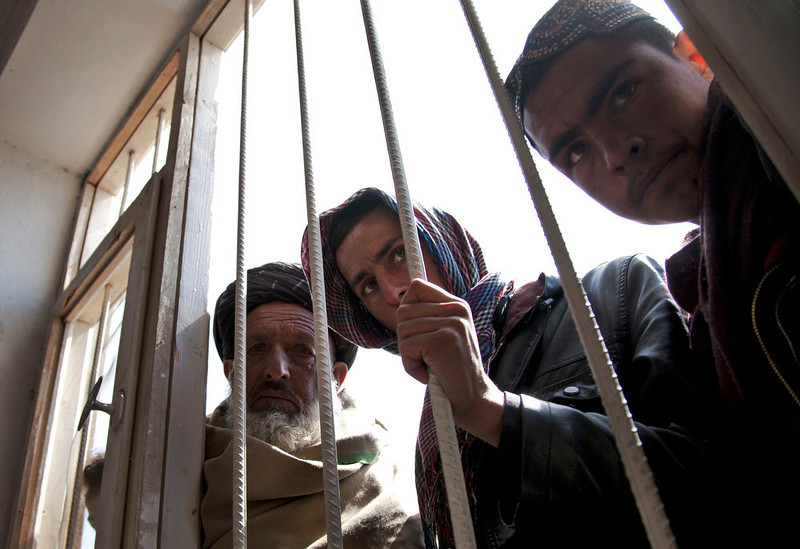 . Afghan men pear through a window with bars as villagers, unseen, tell their stories of abuse, forced detentions and mass arrests by U.S. Special Forces in Maidan Shahr, Wardak province, Afghanistan, Sunday, March 10, 2013. Afghan President Hamid Karzai, infuriated by villager reports of forced detentions and mass arrests, gave U.S. Special Forces two weeks to vacate Wardak province, located barely 30 kilometers (24 miles) from the Afghan capital of Kabul. The deadline for their withdrawal expired midnight Sunday, March 10, 2013. (AP Photo/Anja Niedringhaus)