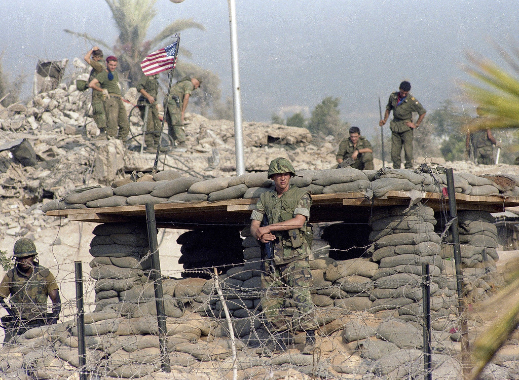 . In this Sunday, Oct. 23, 1983 file photo, U.S. Marines stand guard at a bunker in front of the Marine barracks building that was destroyed by a suicide truck bomb attack that killed 241 American service members near Beirut airport, Lebanon. Marines in the background dig in the rubble to retrieve injured and dead. (AP Photo/Bill Foley, File)