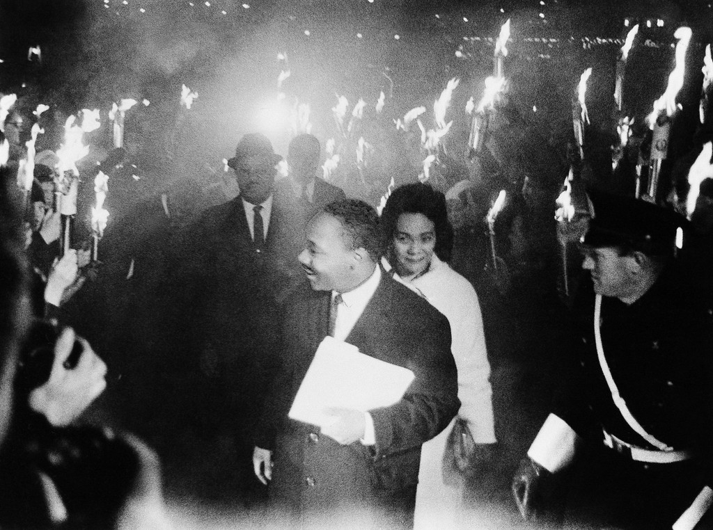 . In smoke and fire from hundreds of torches, Dr. Martin Luther King arrives with his wife Coretta Scott King, to deliver the traditional address of the winner of Nobel Peace Prize at the University of Oslo\'s Festival Hall, Dec. 11, 1964. Behind left: Rev. Ralph Abernathy, who Dr. King especially introduced as his trusted comrade from 13 times in jail together. (AP Photo)
