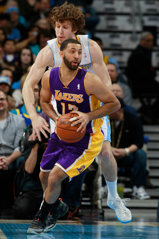 . Los Angeles Lakers guard Kendall Marshall, front, looks to pass ball under pressure from Denver Nuggets forward Jan Vesely, of the Czech Republic, in the fourth quarter of the Nuggets\' 134-126 victory in an NBA basketball game in Denver on Friday, March 7, 2014. (AP Photo/David Zalubowski)