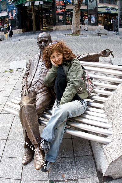 Moran finds a place to sit aside an old man's statue near Moulin rouge place