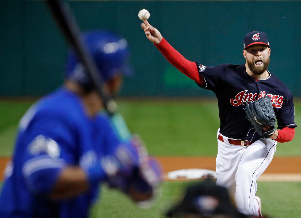. Cleveland Indians starting pitcher Corey Kluber, right, throws to Toronto Blue Jays\' Edwin Encarnacion during the first inning in Game 1 of baseball\'s American League Championship Series in Cleveland, Friday, Oct. 14, 2016. (AP Photo/Gene J. Puskar)