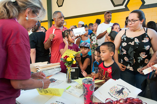 08/28/18 Wesley Bunnell | Staff New Britain High School teacher Sandy Fraioli, L, places a sticker on Derek Suarez's , age 6 middle, booklet during the CSDNB's annual Back to School Bash on Tuesday evening at New Britain Stadium prior to the New Britain Bees game vs the York Revolution. The bash helps introduce students to school staff prior to the school year as well as free admission to the Bees baseball game.