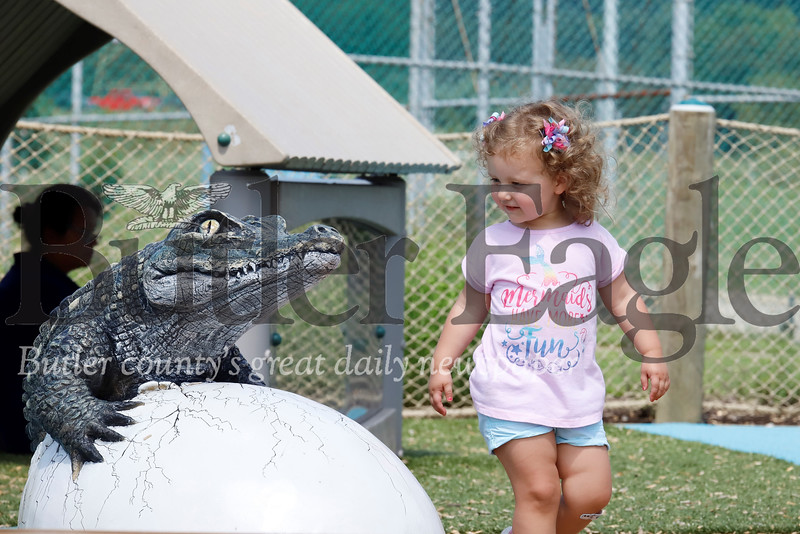 Jennie Langill, 2, of Cranberry strikes up a conversation with one of the crocodiles at Crocodile Cove Playground in North Boundary Park in Cranberry Wednesday. Seb Foltz/Butler Eagle 07/31/19