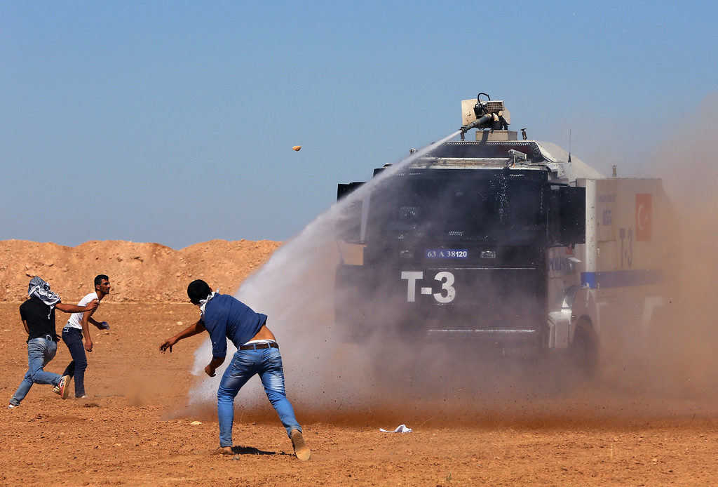. Turkish security forces use teargas and water cannons to disperse protesting local people as several hundred Syrian refugees wait at the border in Suruc, Turkey, Sunday, Sept. 21, 2014. (AP Photo/Burhan Ozbilici)