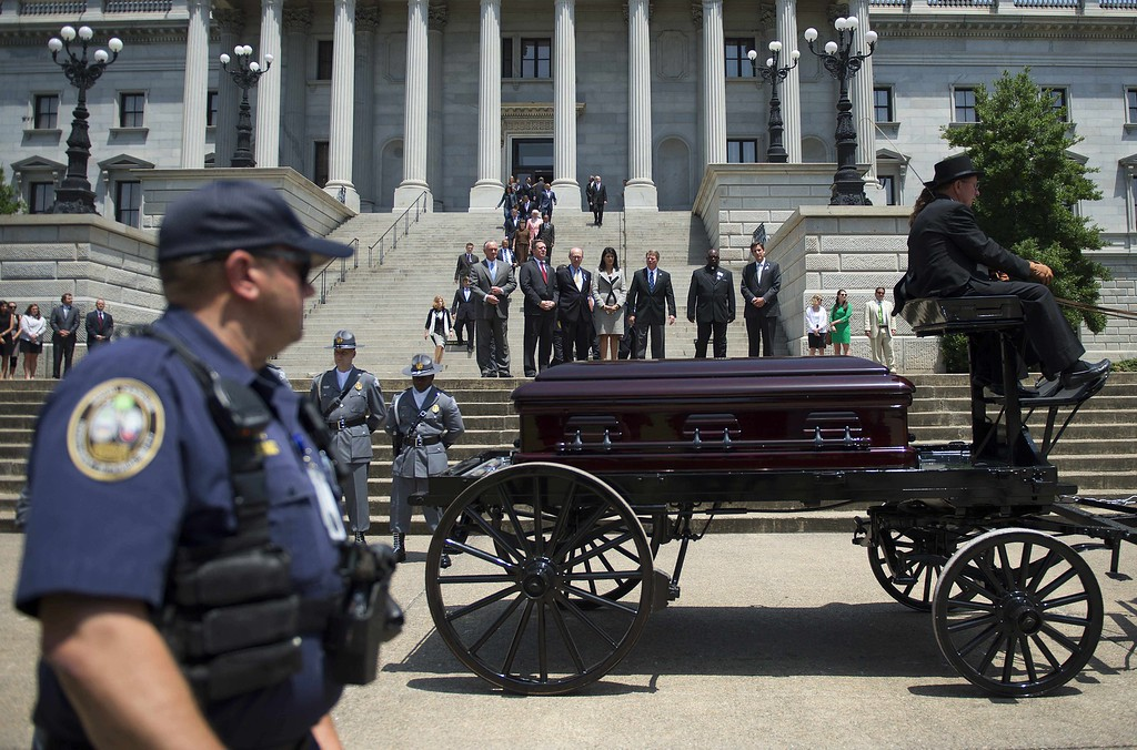 . South Carolina Governor Nikki Haley (C) watches as the coffin of church pastor and South Carolina State Sen. Clementa Pinckney passes before he lies in repose at the Statehouse Rotunda on June 24, 2015 in Columbia, South Carolina. Pinckney was one of nine people killed during a Bible study inside Emanuel AME church in Charleston.  Pressure is growing in South Carolina to take down the Confederate flag that has flies on the front lawn of its State House in Columbia, also alongside a Confederate war memorial. AFP PHOTO/JIM  WATSON/AFP/Getty Images