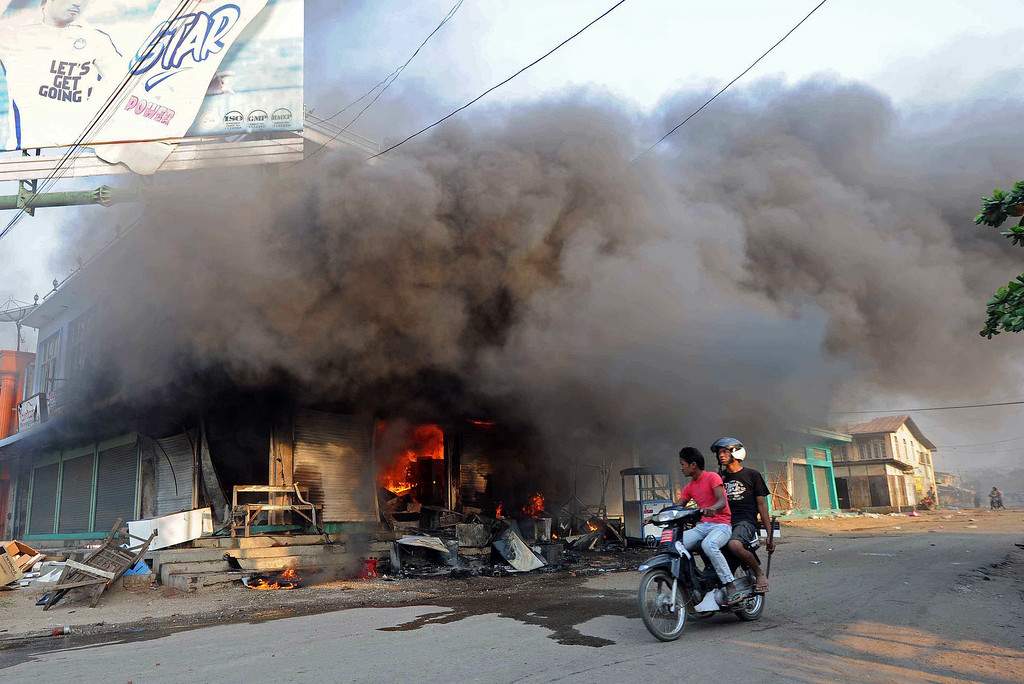 . Residents ride a motorcycle past a burning building in riot-hit Meiktila, central Myanmar on March 22, 2013.   AFP PHOTO/Soe Than WIN/AFP/Getty Images