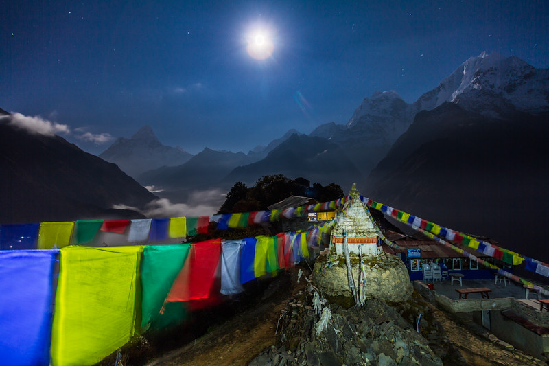 A full moon illuminates the town of Mong La, prayer flags and a Stupa in the Solukhumbu region of Nepal's Sagarmatha National Park in the Himalayas